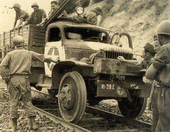 GMC truck as a railroad car seen in Italy. Note the italian soldiers helping americans..jpg