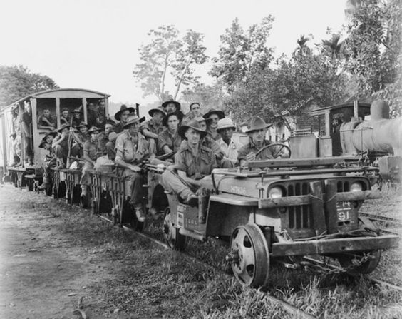 Australian Army jeep train pulling members of the 24th Infantry Brigade. Beaufort, Borneo. 22 July 1945.jpg