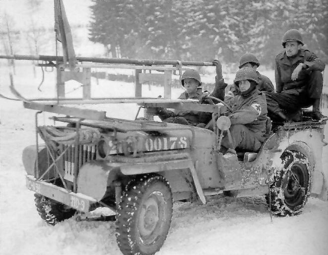 US Jeep of the Medical Detachment, 119th Infantry Regiment (30th Inf Div), ready to pick up casualties. A ski sledge strapped vehicle front, Bulge, Belgium, January 1945.jpg