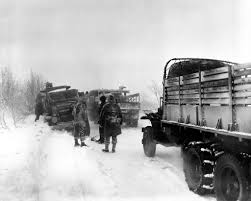 US Trucks Soldiers on road during the Battle of the Bulge.jpg