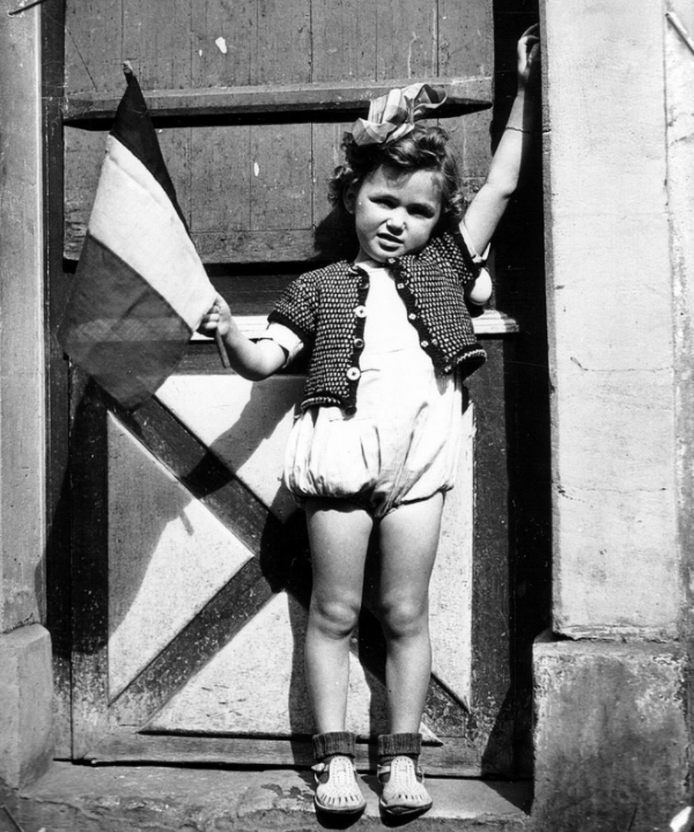 A little French girl stands in the doorway waves the French flag after liberation of her town by the British. Port-en-Bessin-Huppain, Calvados, Lower Normandy, France. July 19.jpg