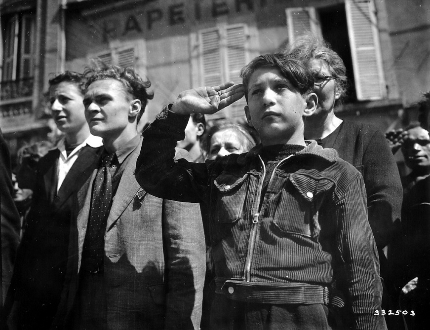 In a group of civilians, a young French boy is the salvation military during the national anthem at Cherbourg.jpg