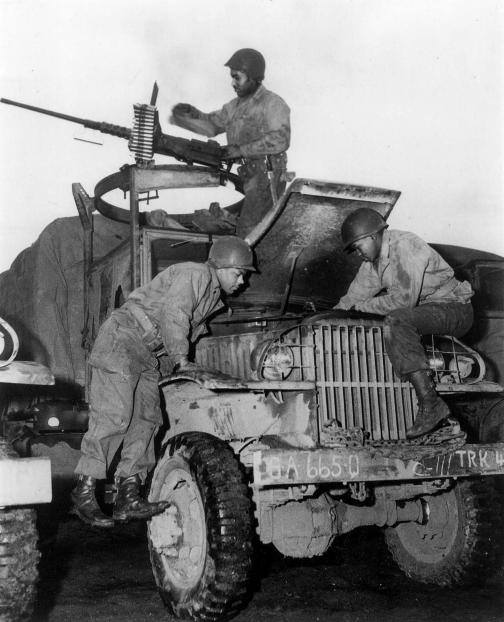 African American members of the World War II Red Ball Express repair a CCKW 2 truck while a crewman at a machine gun keeps watch for aircraf.jpg
