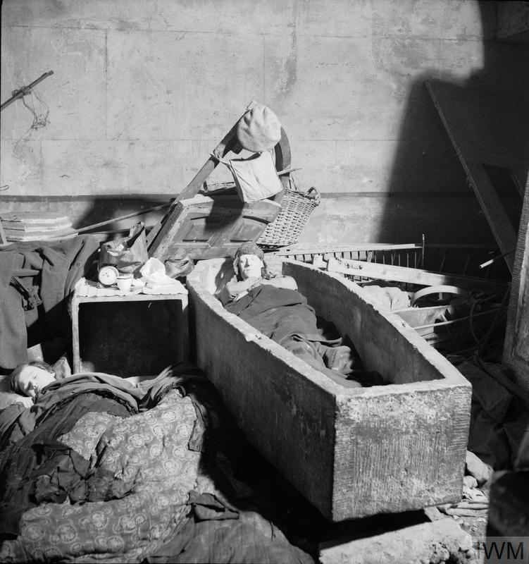 A man sleeping in a stone sarcophagus in an East London church in November 1940..jpg