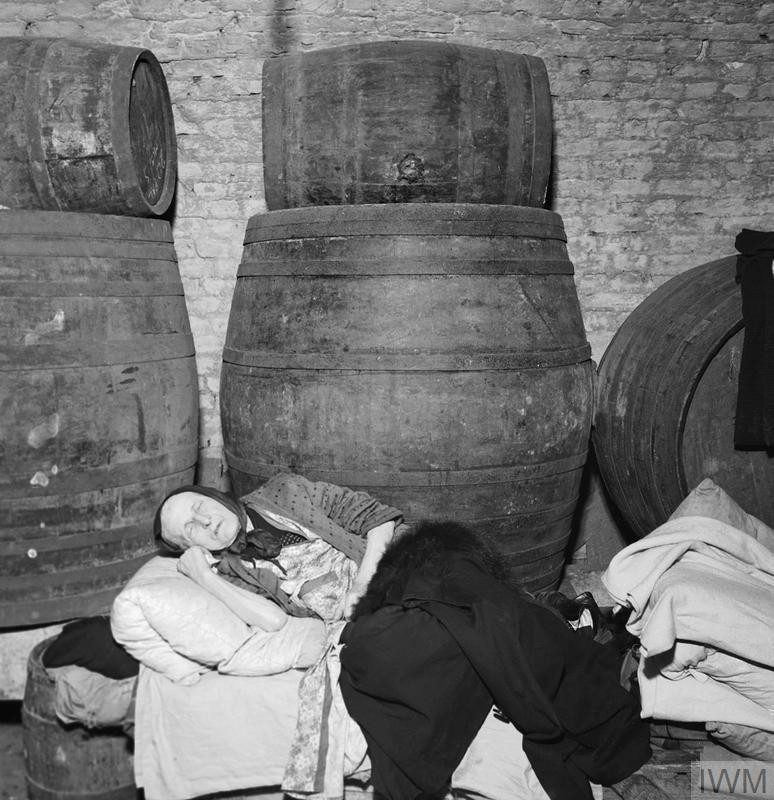 A woman sleeps on a bed made on top of a row of barrels in the cellar of a wine merchant's in East London in 1940.jpg
